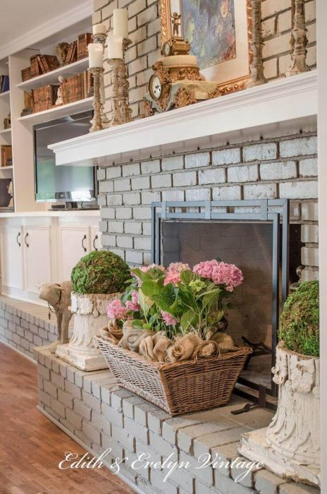 French Country Decor Ideas - Grey Brick Fireplace with Potted Spring Flowers - Cabritonyc.com